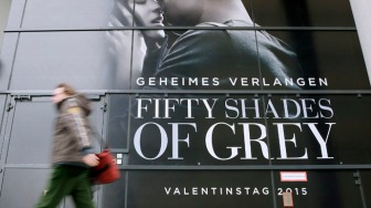 A pedestrian walks past advertisment for film 'Fifty Shades of Grey'  in Berlin